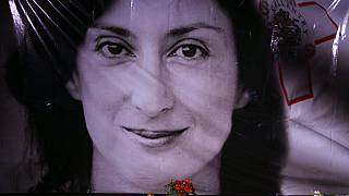 flowers and a candle lie in front of a portrait of slain investigative journalist Daphne Caruana Galizia during a vigil outside the law courts in Valletta, Malta