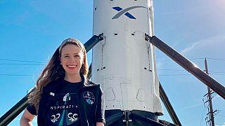 هايلي أرسينو تقف بالقرب من صاروخ سبيس أكس في مقر شركة الطيران في هوثورن في كاليفورنيا.