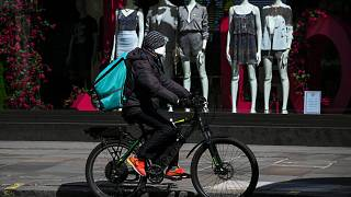 A food delivery rider wears a mask as he rides in a deserted Regent Street, during lockdown to protect against the Coronavirus outbreak, in London, Tuesday, April 14, 2020.