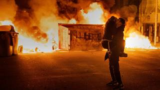 A couple kiss in front of a burning barricade in Barcelona at a protest condemning the arrest of Pablo Hasél
