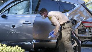 A law enforcement officer looks over a damaged vehicle following a rollover accident involving golfer Tiger Woods, Tuesday, Feb. 23, 2021, in the Rancho Palos Verdes suburb.