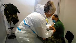 A medical worker gives a shot of COVID-19 vaccine to a Serbian army soldier during the vaccination in Belgrade, Serbia, Tuesday, Jan. 19, 2021.