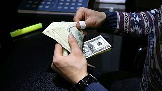 یک صراف ایرانی در حال شمارش دلار آمریکا