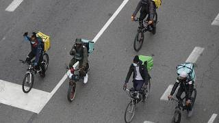 In this Nov. 5, 2020 file photo, food delivery riders stage a protest against the government restriction measures to curb the spread of coronavirus in Milan, Italy.