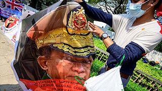 En Tha¨ïlande, un migrant birman tient un poster du général General Min Aung Hlaing (Bangkok, 18 février 2021)