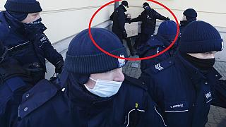 Sarokba szorítanak egy tüntető nőt rendőrök, Varsó, 2021. február 6.
