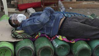 Un hombre duerme sobre bombonas de oxígeno vacías, a la espera de que abra una tienda, en Lima.