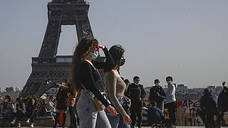 People wearing face masks to prevent the spread of coronavirus walks at Trocadero plaza near Eiffel Tower in Paris, Wednesday, Feb. 24, 2021