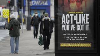 FILE: Pedestrians pass a sign on a bus stop in West Ealing in London, Thursday, Feb. 25, 2021.