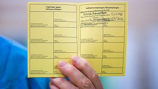 Medical personnel hods a vaccination certificate with a registered Pfizer-Biontech Covid-19 corona virus vaccination at the Favoriten Clinic in Vienna, Austria