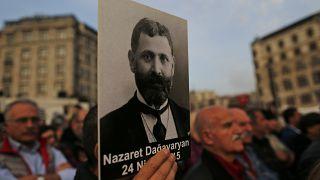 متظاهر يحمل صورة لمثقف أرمني خلال تجمع لإحياء الذكرى السنوية لقتل الأرمن عام 1915 في مدينة إسطنبول.