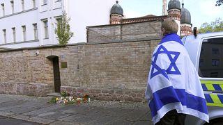 شخص يحمل علم إسرائيل ويقف بجانب زهور وشموع أمام كنيس يهودي في هاله، ألمانيا