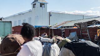 قطعة من زي أحد النزلاء معلقة على الأسلاك الشائكة على جانب سجن كروا دي بوكيه الذي هرب منه العديد من السجناء وقتل فيه عدة أشخاص، كروا دي بوكيه، إحدى ضواحي العاصمة الهايتية