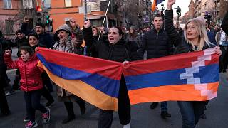 Opposition demonstrators carrying Armenian national and region of Nagorno-Karabakh's flag. Armenia, Saturday, Feb. 27, 2021.
