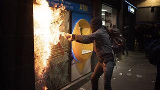 Манифестант поджигает банк в ходе протестов против заключения в тюрьму Пабло Аселя, 27 февраля 2021 г.