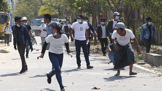 Manifestantes fogem de gás lacrimogéneo disparado pela polícia em Mandalay