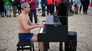 Polish winter swimmers fundraise with Baltic dip and beach piano tunes