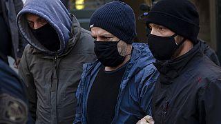 Plain-clothed policemen escort actor-director Dimitris Lignadis
