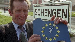 """Il sindaco Norbert Redlinger posa con un orologio """"europeo"""" davanti al cartello di ingresso nella cittadina di Schengen, Lussemburgo, il 24 marzo 1995"""