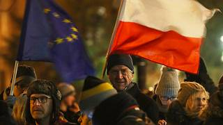 People holding a Poland and EU flags take part in a protest in Warsaw over much-criticised legislation that allows politicians to fire judges who criticize their decisions