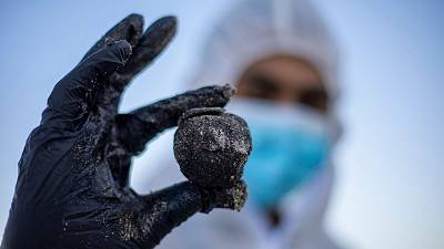 An Israeli soldier wearing a full protective suit holds a piece of tar from an oil spill in the Mediterranean Sea.