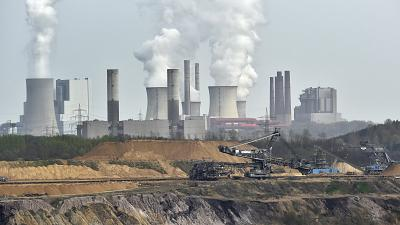 In this April 3, 2014 file photo giant machines dig for brown coal at the open-cast mining Garzweiler in front of a smoking power plant near Grevenbroich, Germany.