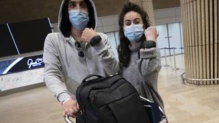 Israeli travelers hold up electronic monitoring bracelets they are required to wear after returning from abroad at the Ben Gurion airport near Tel Aviv