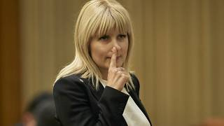 In this Monday, Feb. 9, 2015 file photo, Elena Udrea touches her nose after delivering a speech in parliament pleading with fellow lawmakers not to approve her arrest.