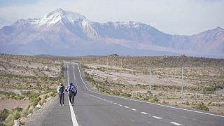 Migrantes venezolanos caminan por una carretera en el desierto de Atacama, Chile