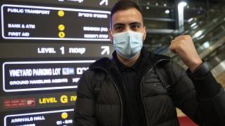 A traveler holds up an electronic monitoring bracelet