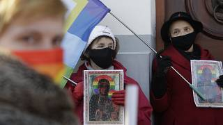 Polish LGBT rights activists gather outside a court which acquitted three women who faced trial on accusations of desecration, in Plock, Poland, Tuesday March 2, 2021