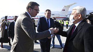 Serbian President Aleksandar Vucic, left, and Muslim member of the tripartite Presidency of Bosnia Sefik Dzaferovic exchange fist bumps at Sarajevo Airport.