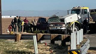 In this image from KYMA, law enforcement work at the scene of a deadly crash involving a semi-truck and an SUV in Holtville, Calif., on Tuesday, March 2, 2021. (KYMA via AP)