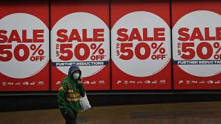 A woman wearing a face covering walks past a shop window in London, Thursday, Jan. 14, 2021 during England's third national lockdown to curb the spread of coronavirus.
