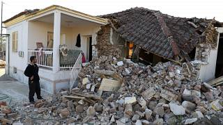 Ein Mann steht neben seinem zerstörten Haus im griechischen Mesochori.
