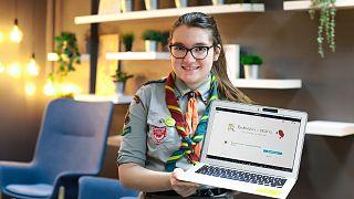 En la imagen Krysia Paszko vestida con su uniforme de los Boy Scouts muestra la página falsa de cosméticos que ha creado.
