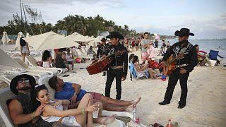 Dos mariachis hablan con turistas en Playa del Carmen, en el estado mexicano de  Quintana Roo.