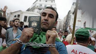 متظاهر يربط يديه بشكل رمزي ويظهر جواز سفره خلال مظاهرة في الجزائر العاصمة، 20 سبتمبر/ أيلول 2019