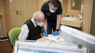 Gulyás Gábor háziorvos a meglévő betegségeiről kérdezi egyik páciensét rendelőjében, mielőtt beoltja Nyíregyházán 2021. március 3-án