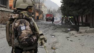 Katona védi a tűzoltókat, akik egy bombatámadás helyszínén dolgoznak