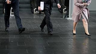 Business men and women walk in the City of London
