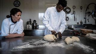 Mamadou Yaya Bah prépare du pain aux côté de Patricia Hyvernat à la Chapelle du Châtelard dans l'Ain