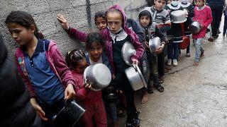 أطفال فلسطينيون ينتظرون تلقي وجبات مجانية في قطاع غزة.