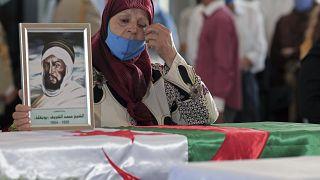 جزائرية تبكي على نعش واحد من 24 جزائريًا تم إعادة بقاياهم بعد إعدامهم في الجزائر العاصمة.