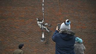 Members of the public pause to look at an artwork by street artist Banksy on the side of Reading Prison in Reading, west of London.