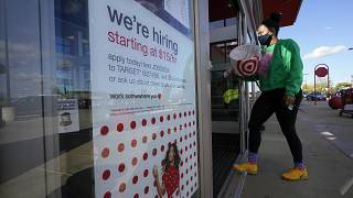 In this Sept. 30, 2020, file photo, a passerby walks past a hiring sign while entering a Target store in Westwood, Mass.