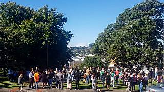 People gather on high ground in Whangarei, New Zealand, as a tsunami warning is issued