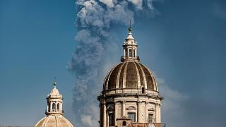 Smoke billows from a crater of Mount Etna volcano behind the dome of the Catania Saint Agatha cathedral in Catania, southern Italy. March 4, 2021.