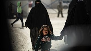 A woman and children are pictured at the Kurdish-run al-Hol camp
