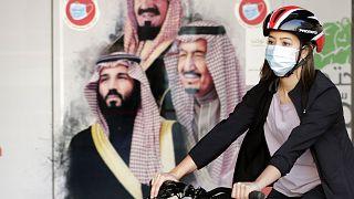 Die saudische Radsportlerin Sawsan Abdel Fattah fährt vor einem Plakat, das den  saudischen König Salman und seinen Kronprinzen Mohammed bin Salman zeigt.